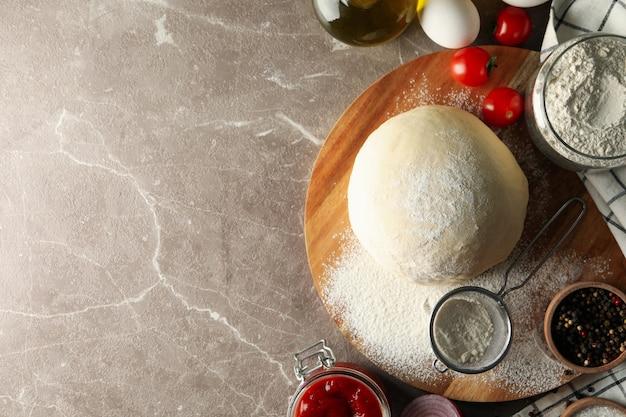 Massa e ingredientes para cozinhar pizza em fundo cinza