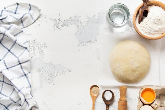 Massa e ingredientes para o preparo de massas, massas, ovos, farinha, água e sal sobre uma mesa velha e leve e rústica