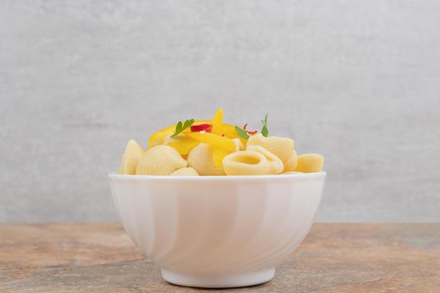 Massa em forma de concha com fatias de vegetais em uma tigela branca.