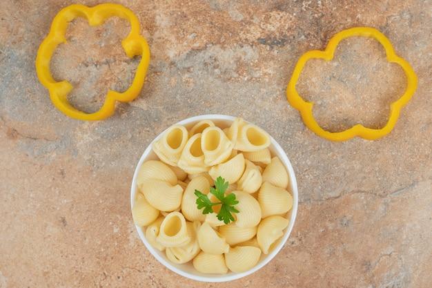 Massa em forma de concha e fatias de pimenta em fundo laranja