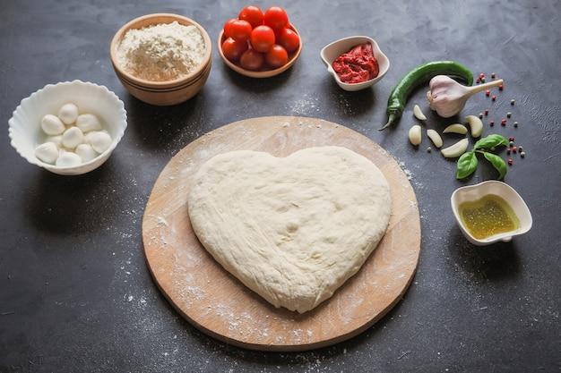 Massa em forma de coração e um conjunto de ingredientes para pizza em uma mesa preta. vista do topo