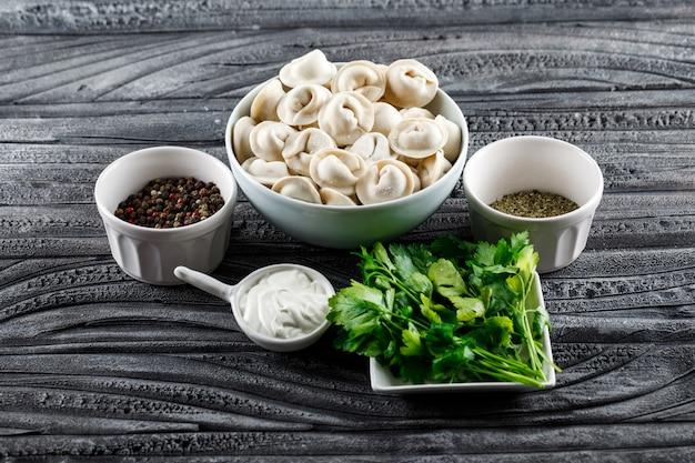 Massa em uma tigela com verduras, especiarias, vista de alto ângulo sobre uma superfície de madeira cinza