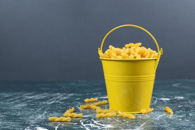 Massa espiral crua no balde amarelo.