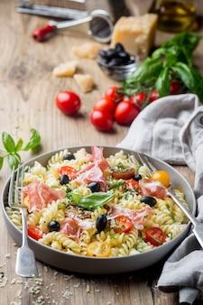 Massa espiral de fusilli italiana com tomate uva, azeitonas, presunto e queijo parmesão em um prato