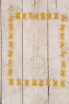Massa farfalle formando moldura em fundo de madeira