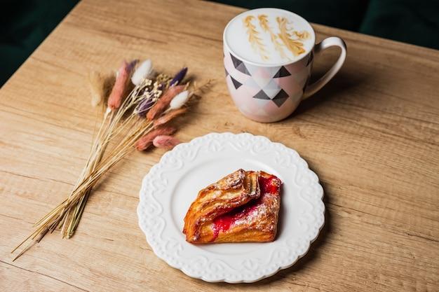 Massa folhada com geléia vermelha em um prato branco, uma caneca de café branco liso e flores