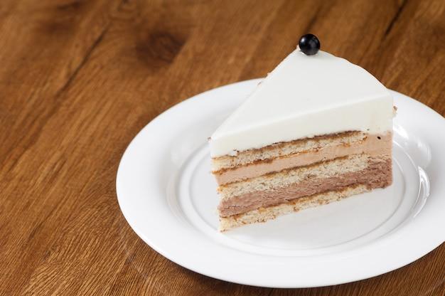 Massa folhada em um prato redondo branco sobre uma superfície de madeira com reflexo
