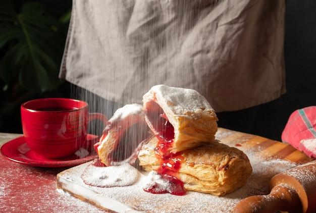 Massa folhada sobremesa geléia vermelha mão viburno cereja xícara café fundo preto
