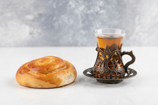 Massa fresca rodopiada com copo de chá em uma superfície branca
