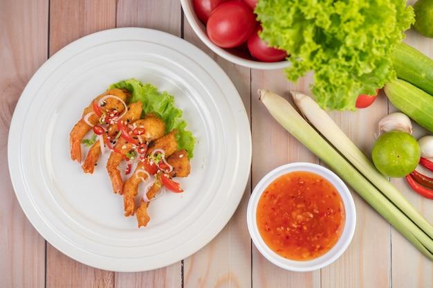 Massa frita de camarão organizada lindamente em um prato branco.