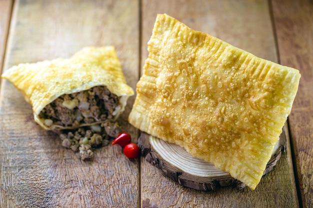 Massa frita recheada com carne moída e batata, molho picante servido quente.