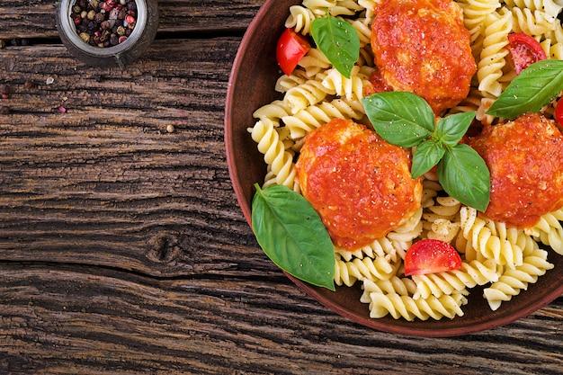 Massa fusilli com almôndegas em molho de tomate e manjericão na tigela, cozinha italiana, vista superior, configuração plana
