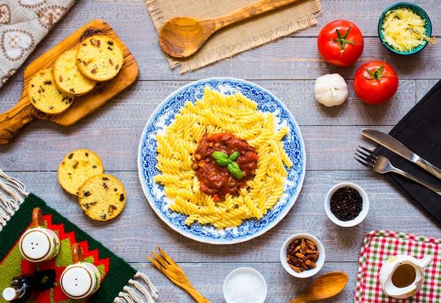 Massa fusilli com molho de tomate, tomate, cebola, alho, páprica seca, azeitonas, pimenta e azeite de oliva em uma mesa de madeira