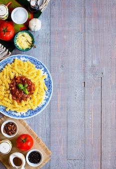 Massa fusilli com molho de tomate, tomate, cebola, alho, pimentão seco, azeitonas, pimenta e azeite, sobre um fundo de madeira.