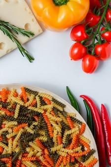 Massa fusilli com tomate, pimentão, planta no queijo em um prato na mesa branca, plana leigos.