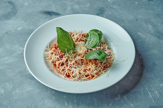 Massa italiana à bolonhesa com molho vermelho, carne moída e queijo em um prato branco sobre uma superfície cinza