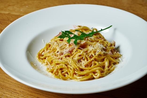 Massa italiana caseira em molho cremoso, bacon e parmesão em um prato branco. cozinha italiana .. mesa de fotos de comida saborosa
