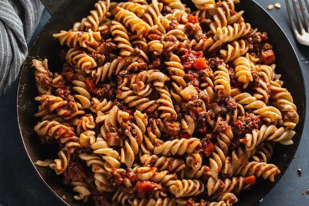 Massa italiana clássica com carne picada e legumes cozidos e servidos na panela. fechar-se.