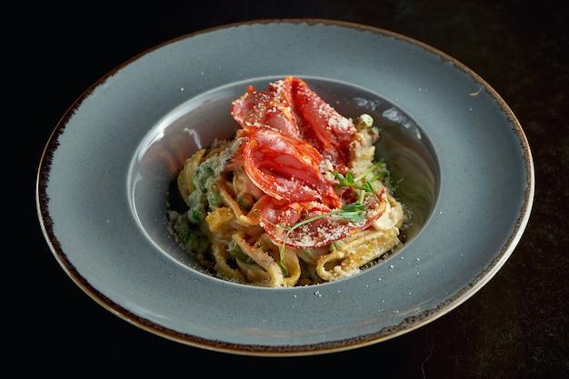 Massa italiana com cogumelos chanterelle e chouriço, queijo parmesão em um prato cinza sobre um fundo preto. fechar-se