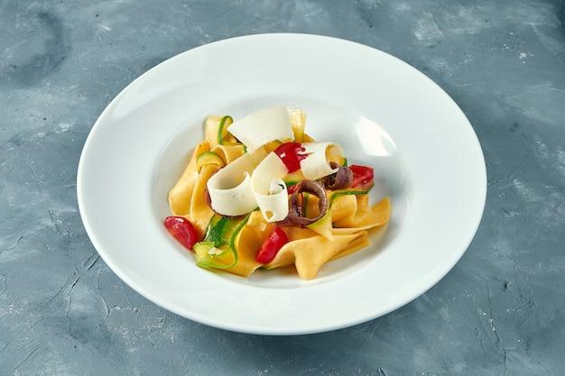 Massa italiana com legumes, parmesão e anchovas em uma tigela branca sobre a superfície de concreto