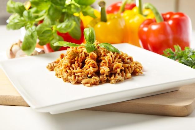 Massa italiana com pesto de pimenta vermelha servida em prato branco e decorada com manjericão