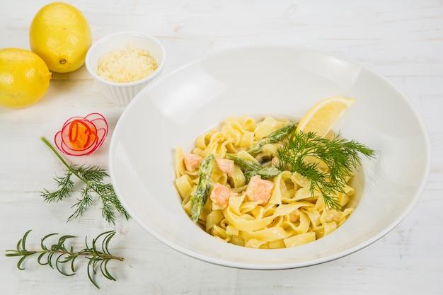 Massa italiana com salmão e ervas na mesa branca