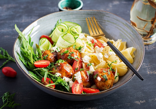 Massa italiana. conchiglie com almôndegas, queijo feta e salada na mesa escura. jantar. conceito de slow food