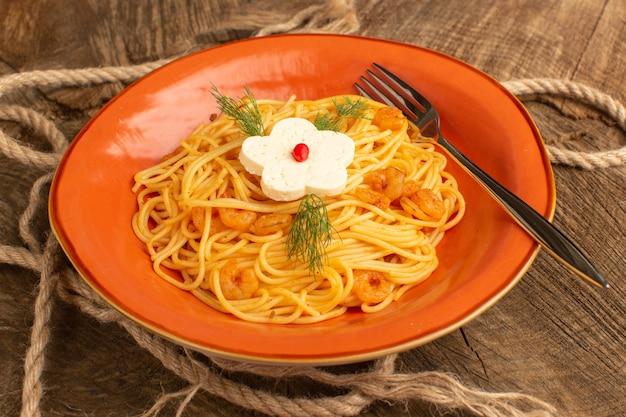 Massa italiana cozida com verduras dentro do prato laranja na madeira