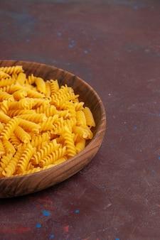 Massa italiana crua com pouca formação dentro do prato na secretária escura