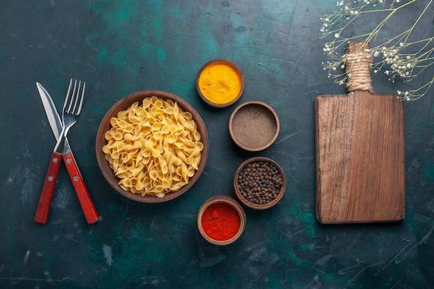 Massa italiana crua com temperos em fundo azul escuro, vista de cima, ingrediente alimentar cru