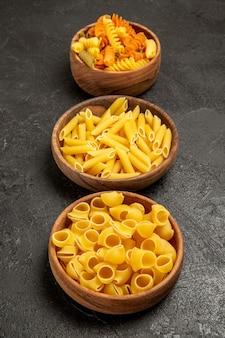 Massa italiana crua de frente forma diferente formada dentro de pratos no espaço cinza