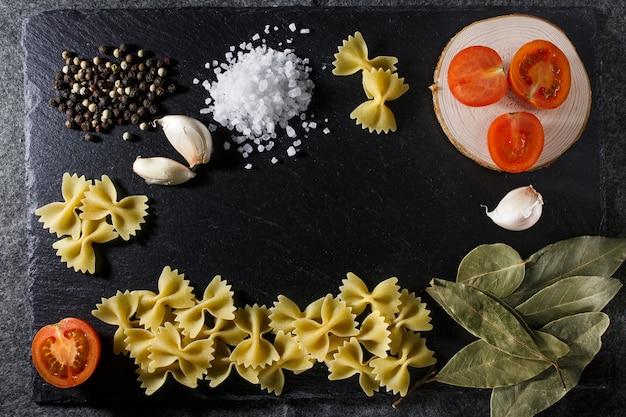 Massa italiana crua e composição dos ingredientes da grão inteira no fundo preto da pedra da ardósia rústica
