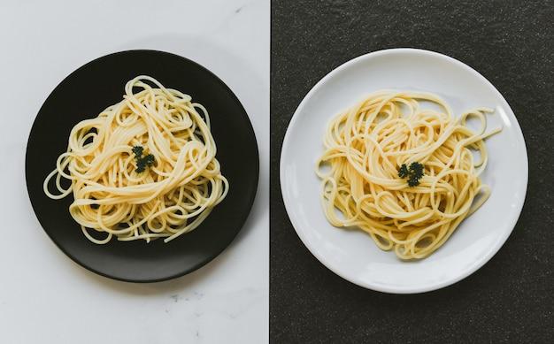 Massa italiana de espaguete servida no prato branco e conceito de comida e menu de espaguete de chapa preta com ruído grunge e vista superior