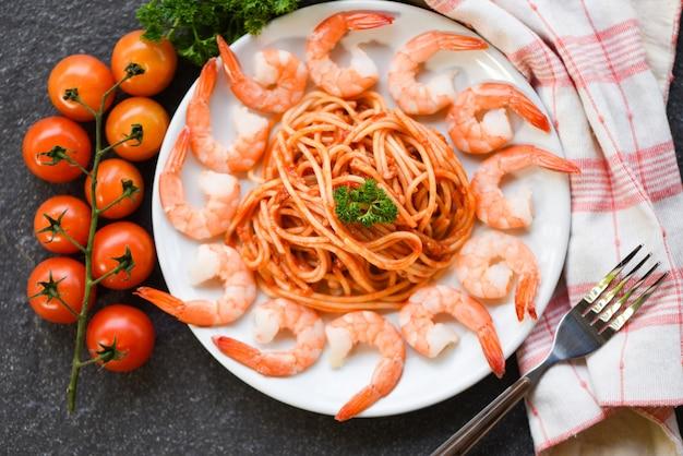 Massa italiana de esparguete à bolonhesa com camarão camarão servido no prato branco com tomate