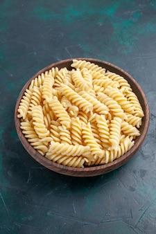 Massa italiana deliciosa de frente olhando dentro de uma panela marrom na mesa azul escura