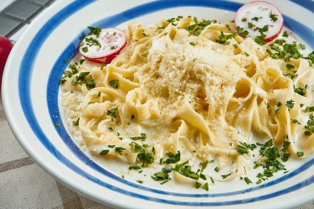 Massa italiana do fettuccine no molho de queijo com parmesão, tomate cereja e ervas na bacia cerâmica branca na superfície branca.