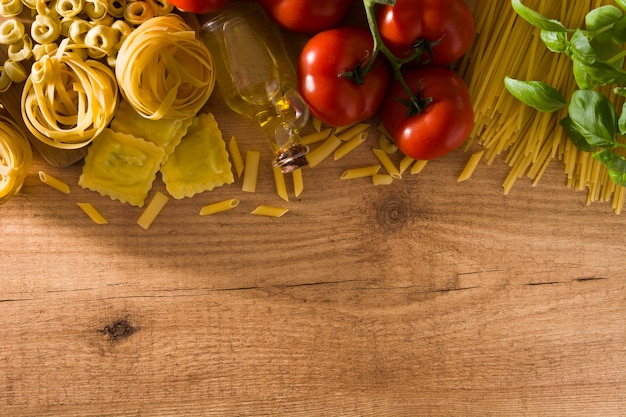 Massa italiana e ingredientes. ravioli, macarrão penne, espaguete, tortellini, tomate e manjericão na mesa de madeira