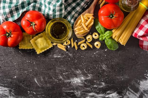 Massa italiana e ingredientes. ravioli macarrão penne macarrão tortellini tomate e manjericão