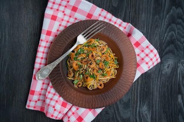 Massa italiana em um molho com camarões em um prato, vista superior. fundo de madeira escuro.