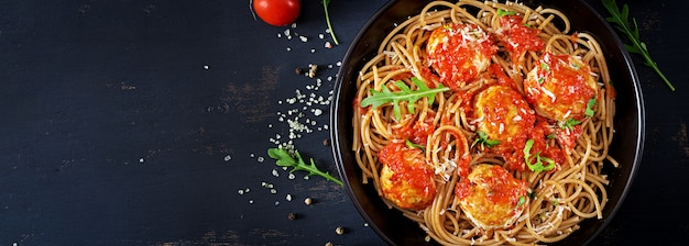 Massa italiana. espaguete com almôndegas e queijo parmesão em chapa preta na mesa de madeira rústica escura. jantar. vista do topo. conceito de comida lenta