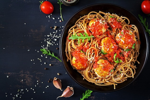 Massa italiana. espaguete com almôndegas e queijo parmesão em chapa preta sobre fundo escuro de madeira rústica. jantar. vista do topo. slow food conceito