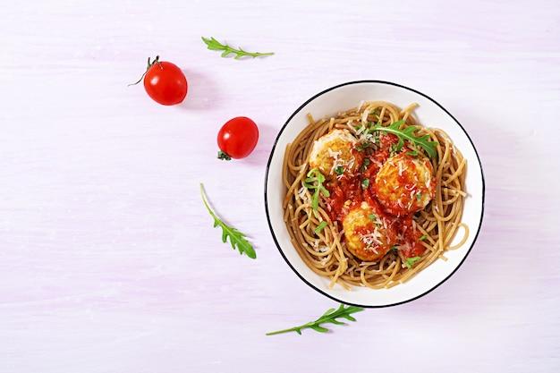 Massa italiana. espaguete com almôndegas e queijo parmesão na tigela sobre fundo claro de madeira rústica. jantar. vista do topo. slow food conceito