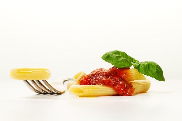 Massa italiana espaguete cozinhada apetitosa colorida saboroso com molho de tomate bolognese e manjericão fresca na forquilha. serviço criativo, closeup.