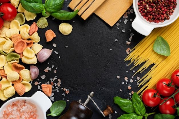 Massa italiana orecchiette com ingredientes tradicionais para o preparo de alimentos na mesa preta. fundo de cozimento de alimentos culinários. vista do topo.