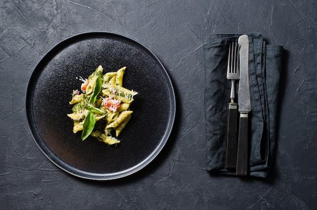 Massa italiana penne com espinafre, tomate cereja e manjericão. ingredientes para cozinhar.