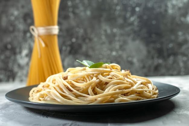 Massa italiana saborosa de frente com massa crua em prato de refeição de cor escura.