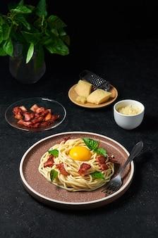 Massa italiana tradicional carbonara com bacon, queijo e gema de ovo no prato em fundo escuro