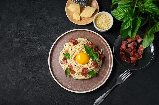 Massa italiana tradicional carbonara com bacon, queijo e gema de ovo no prato sobre fundo escuro.
