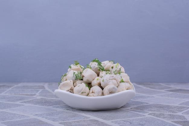 Massa khinkali caucasiana em um prato branco com ervas e especiarias