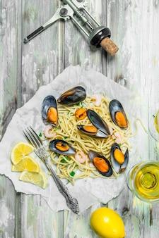 Massa mediterrânea. espaguete com frutos do mar, amêijoas e vinho branco. sobre uma superfície rústica.